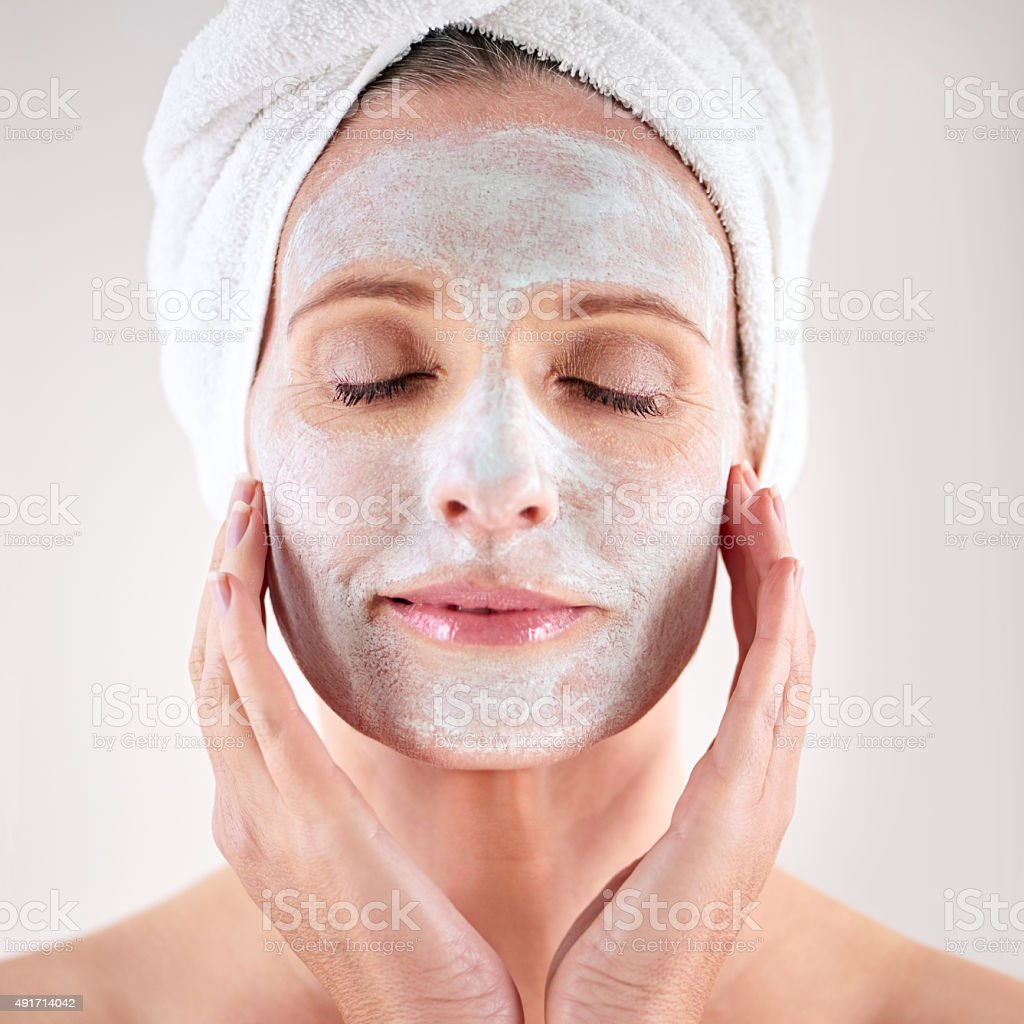 Pampering her skin with a facial treatment stock photo