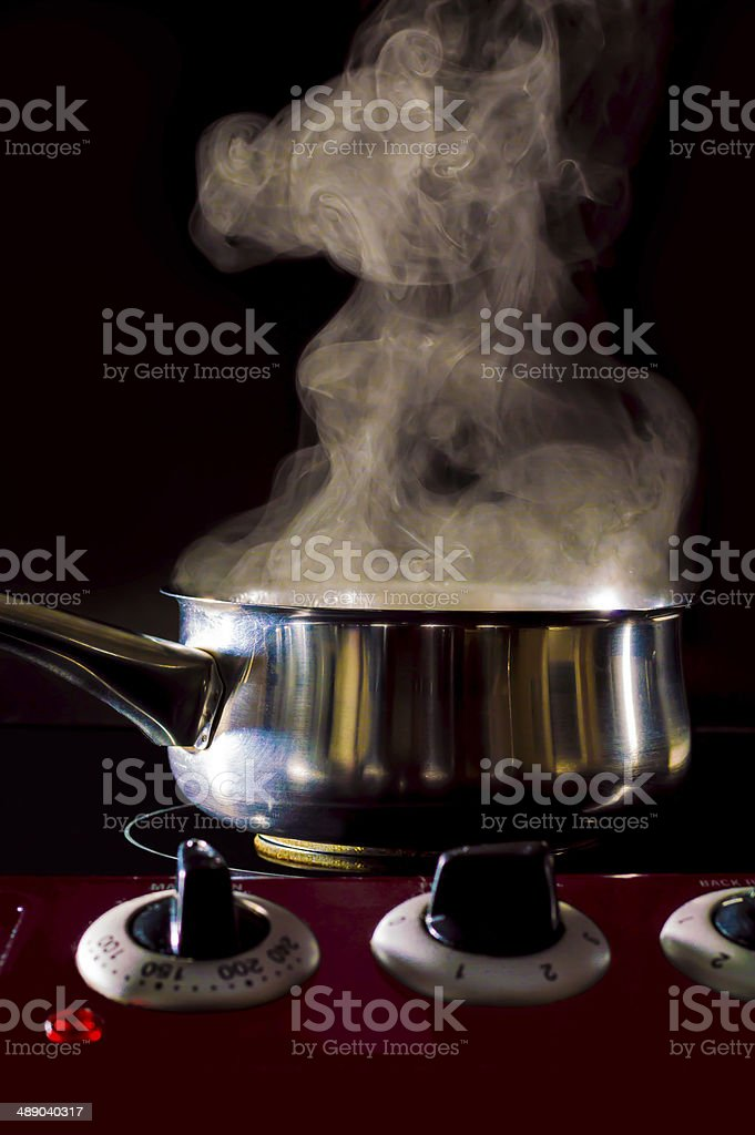 pan boiling on hob  cooker, black background, steam, stock photo