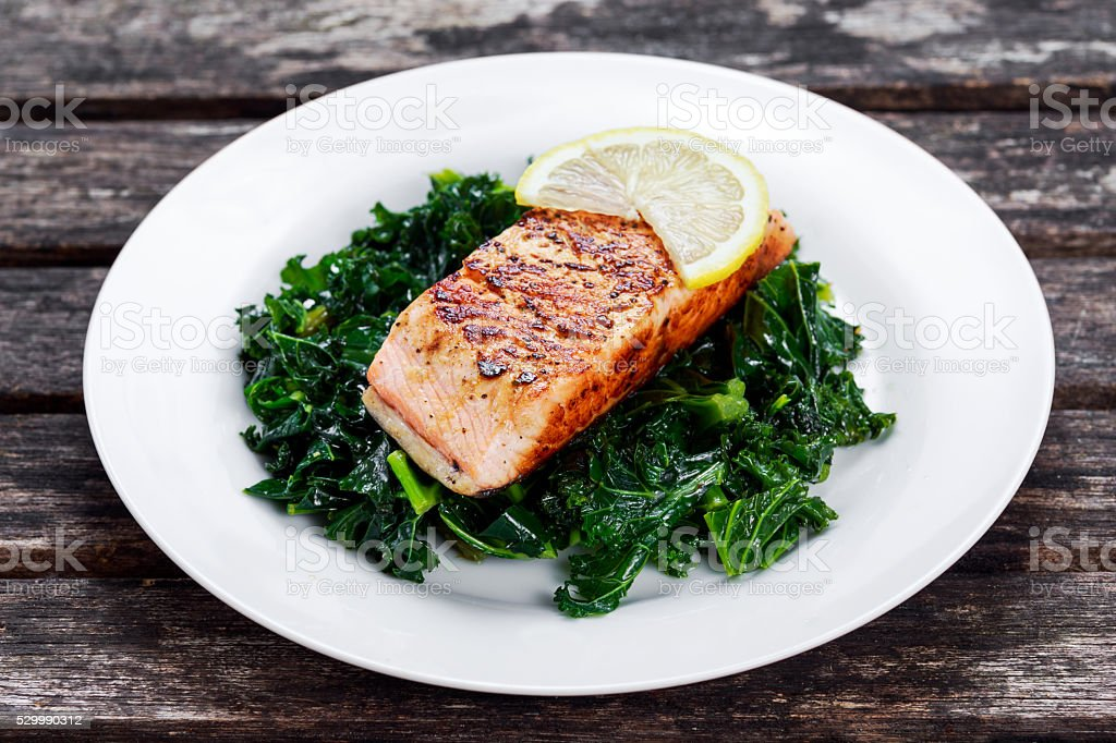 Pan fried Salmon Served with Kale on plate stock photo