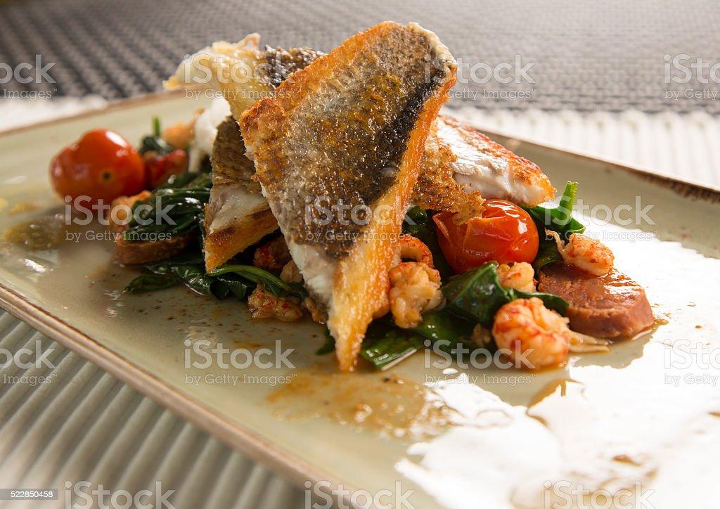 Pan fried sea bass with crayfish, chorizo & baby spinach stock photo