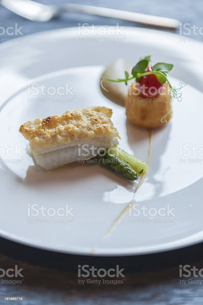 Pan fried snapper with a parmesan crust and baby vegetables royalty-free stock photo