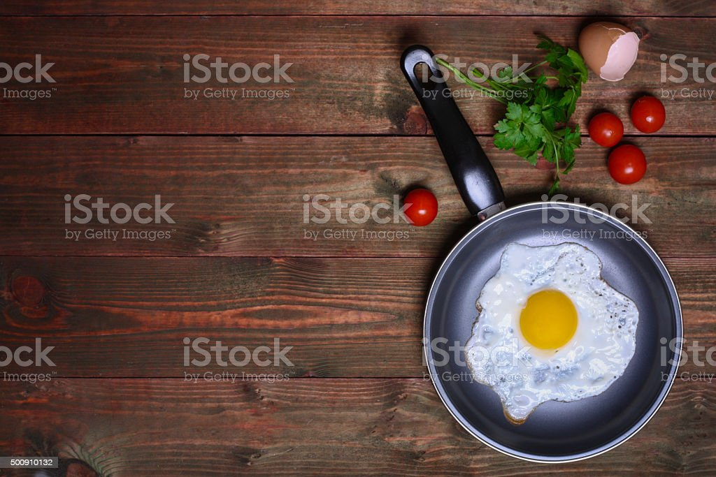 Pan of fried egg, with cherry-tomatoes and parsley stock photo