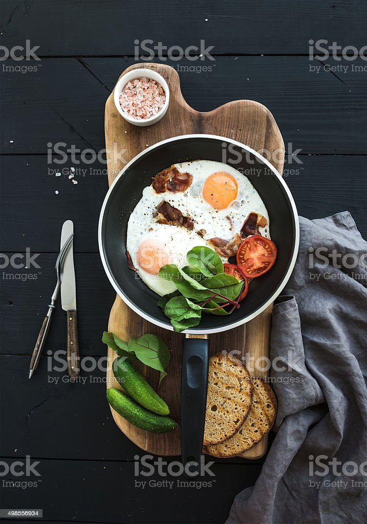Pan of fried eggs, bacon, tomatoes with bread, mangold and stock photo