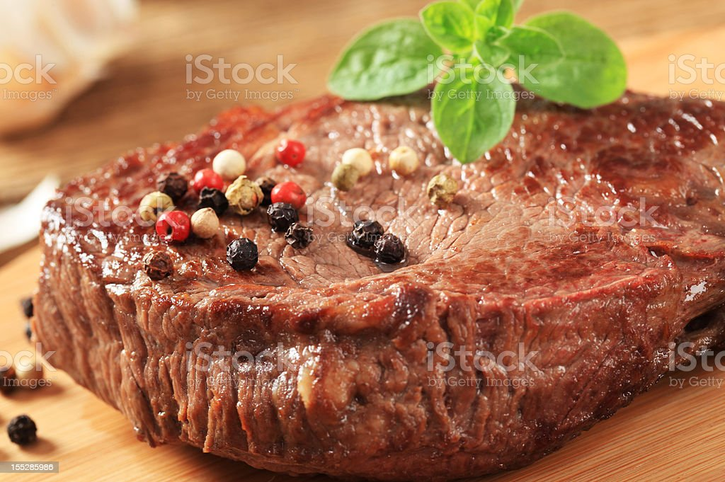 Pan seared beef steak with tri-colored peppercorns and basil stock photo
