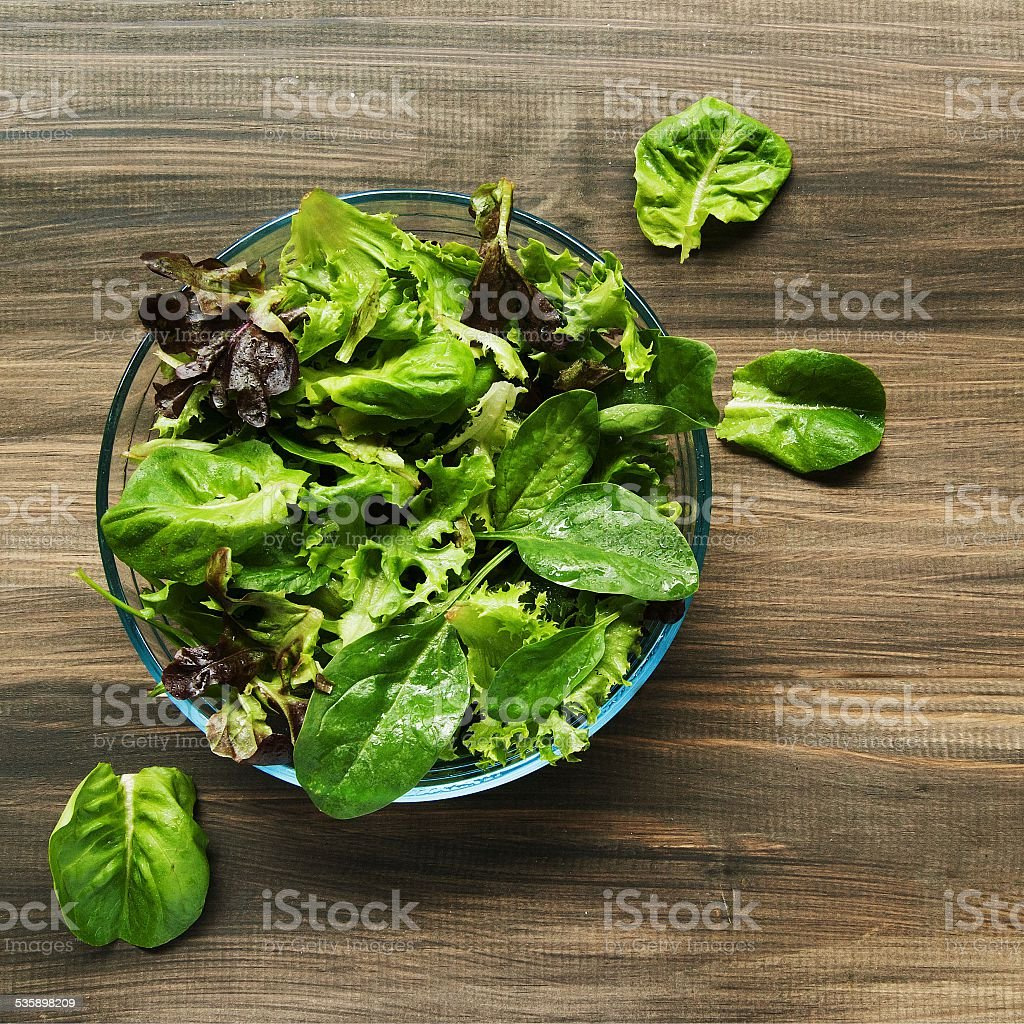 Pan with a green salad on wooden boards stock photo