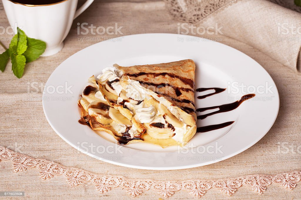 pancake with banana and whipped cream in a still life stock photo