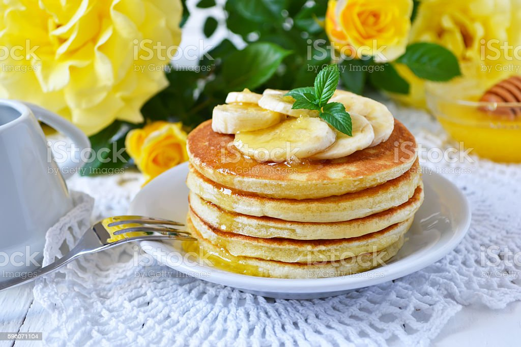 Pancake with banana, covered with honey or maple syrup stock photo