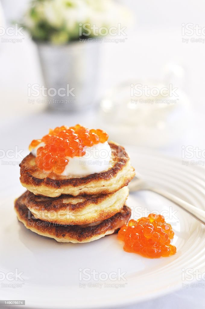 Pancake with sour cream and red caviar stock photo