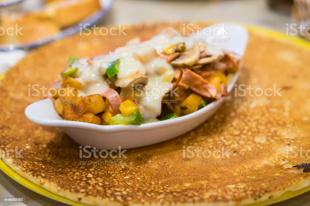 Pancake with turkey bacon, ham, mushroom, and cheese. Food background stock photo