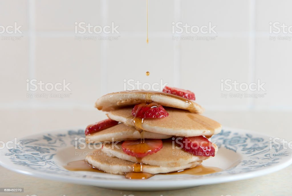Pancakes covered in strawberries and syrup. stock photo