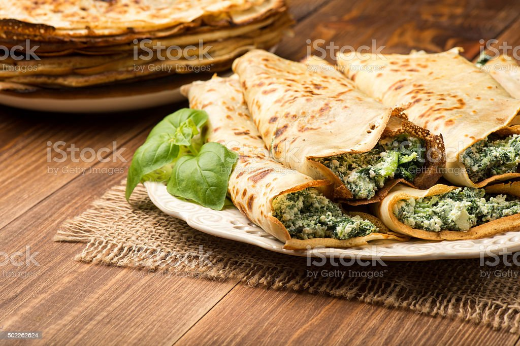 Pancakes filled  with spinach and cheese  on the wooden surface. stock photo