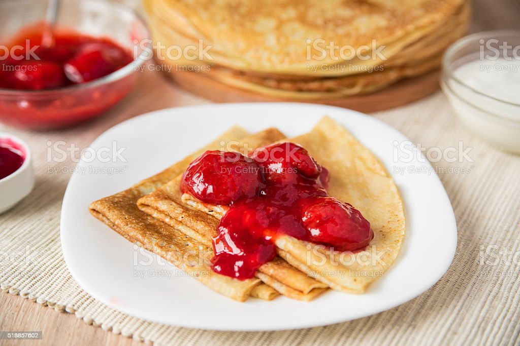 Pancakes folded triangle with strawberry sauce on a white plate stock photo