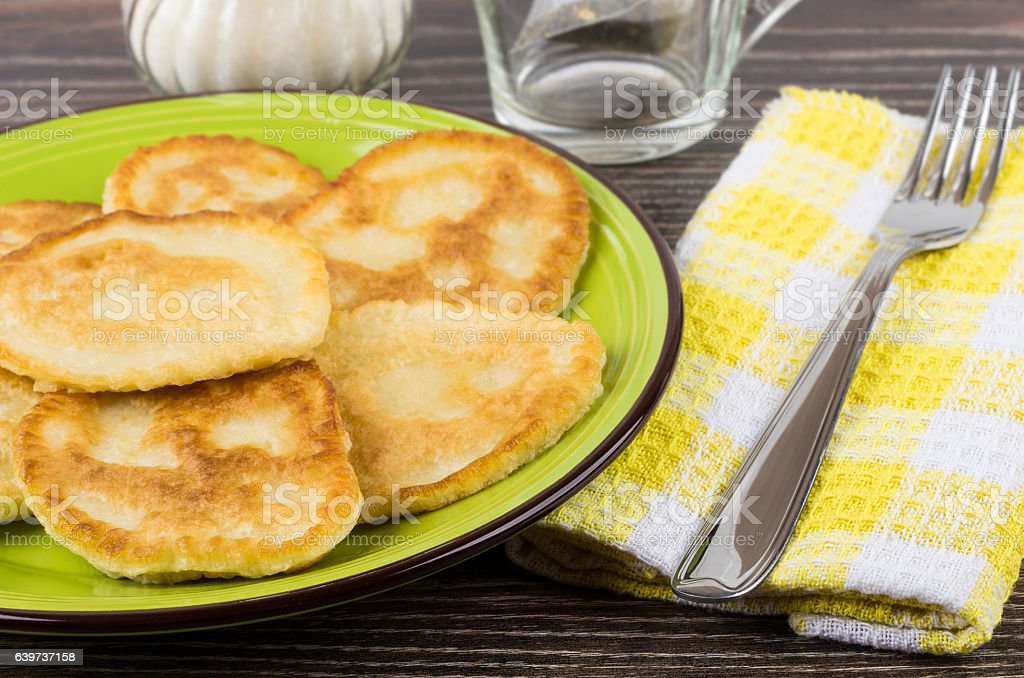 Pancakes in green plate, fork on yellow napkin on table stock photo