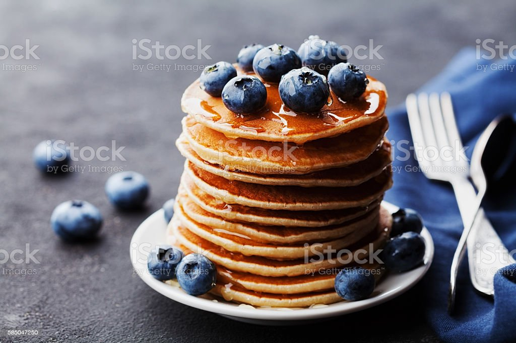 Pancakes or fritters with blueberries and honey syrup stock photo