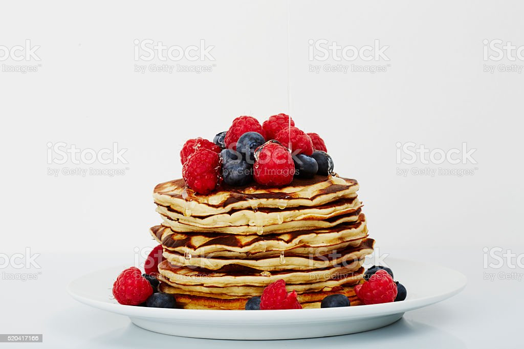 Pancakes topped with fruit and honey in white studio stock photo