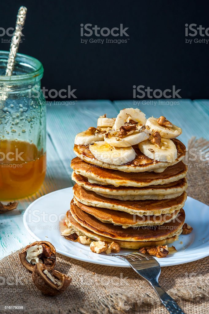 Pancakes with banana slices, honey and walnuts on wooden background. stock photo