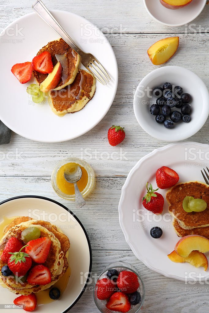 Pancakes with berries for breakfast on white table stock photo