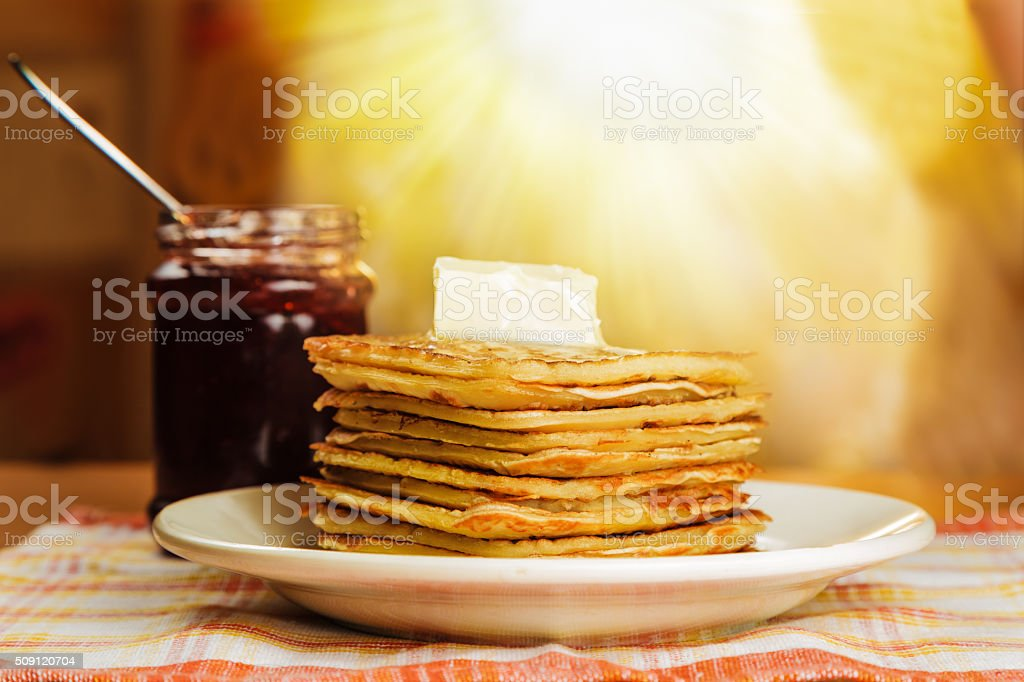 Pancakes with butter and jam on the table stock photo