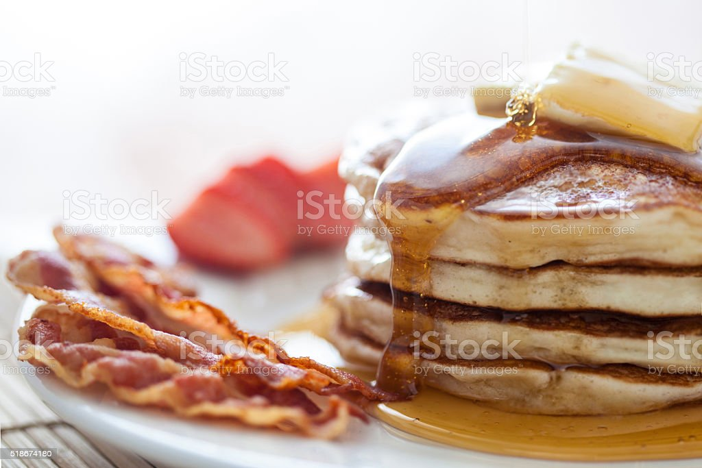 Pancakes with honey, bacon and strawberries stock photo