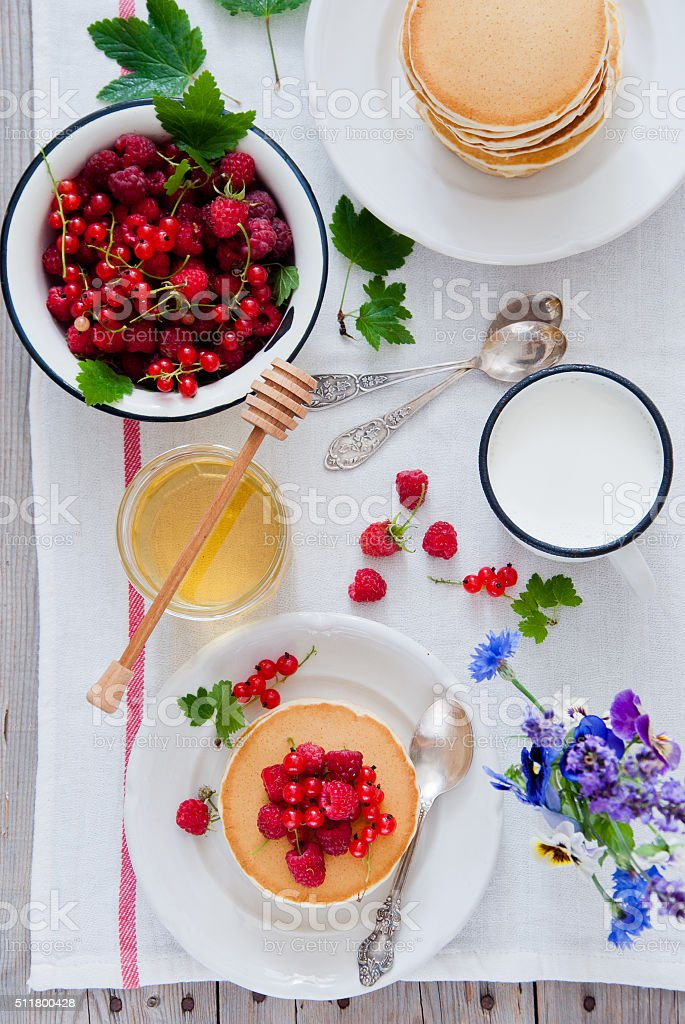 Pancakes with red berries and honey stock photo