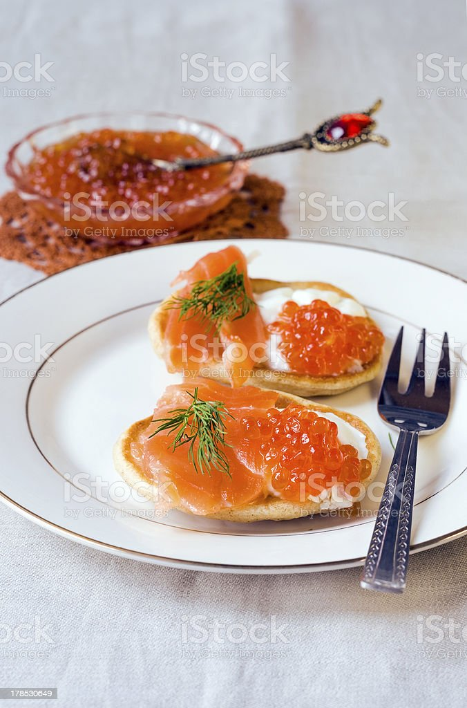 pancakes with red caviar, salmon and cheese stock photo
