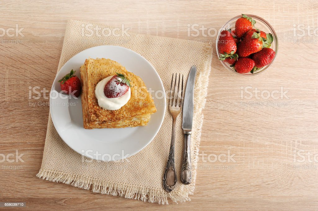 pancakes with sour cream and strawberries in a plate stock photo