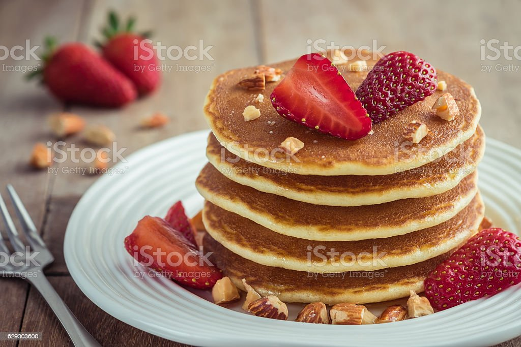 Pancakes with strawberry and almonds on plate stock photo