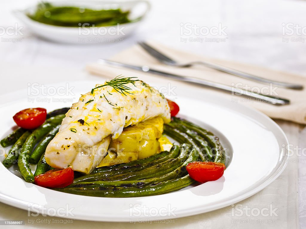 Panfryed monkfish tail with vegetables plated formally stock photo