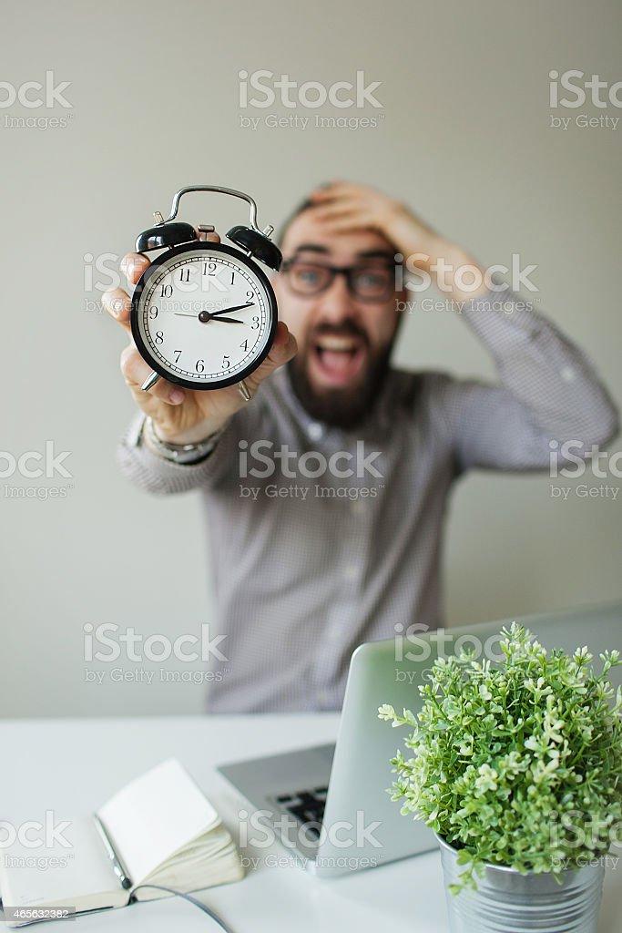 Panic man holds alarm clock and head scared of deadline stock photo