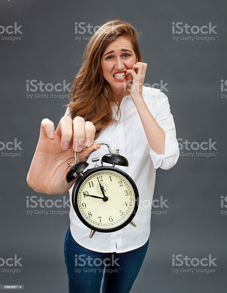 panicking girl showing embarrassing alarm clock for tensed time management stock photo