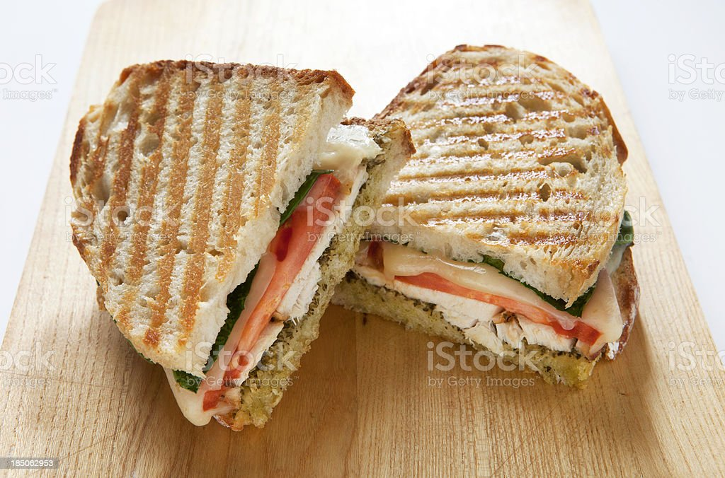 Panini with Chicken and Pesto on a Wooden Cutting Board. stock photo