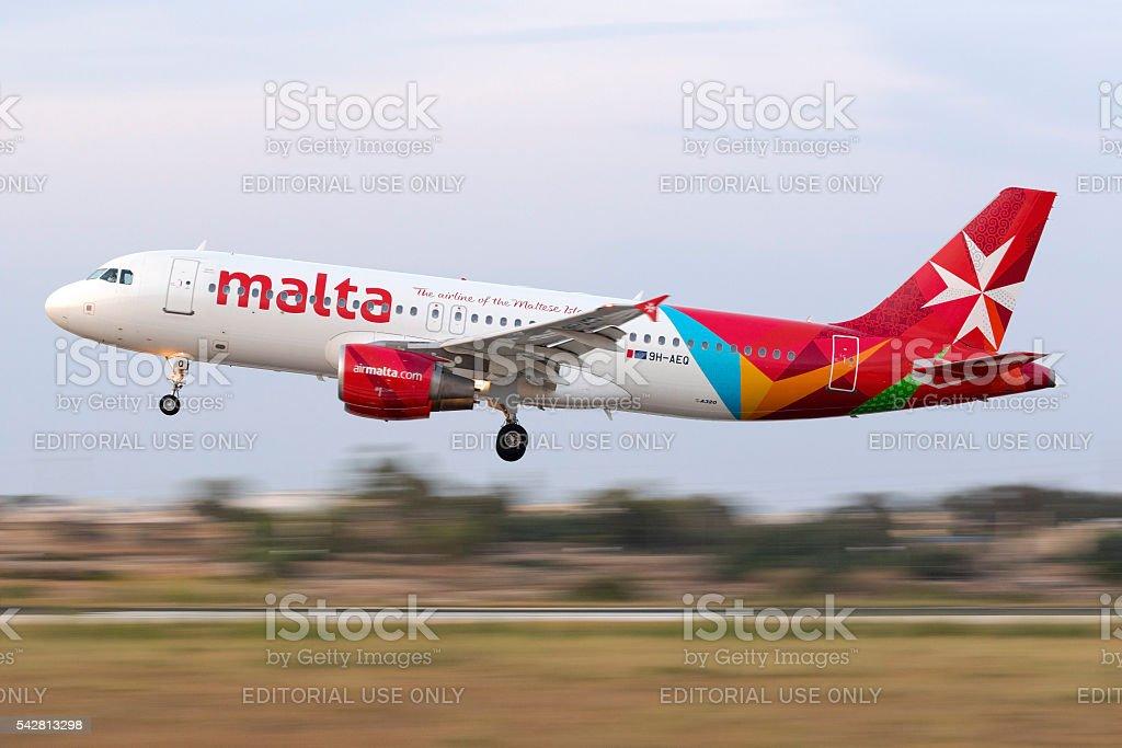Panned shot of an Airmalta Airbus landing stock photo