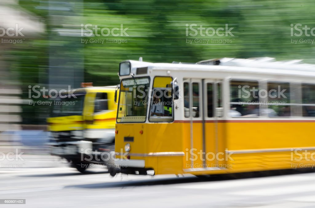 Panning of a passing yellow tramway and truck in Budapest stock photo