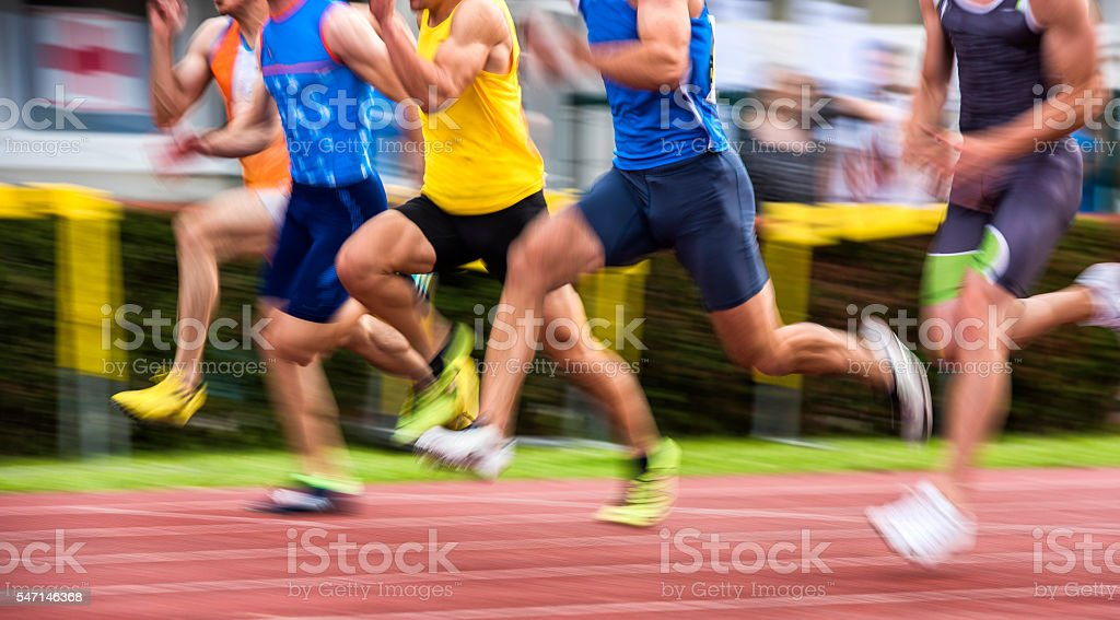 Panning Shot of Group of Athletes at 100m sprint stock photo