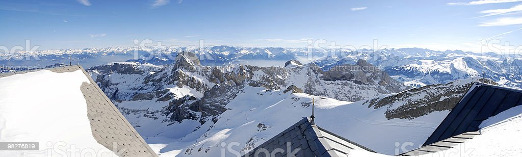 Panorama mountain view over snowed house roof royalty-free stock photo