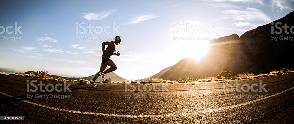 Panorama of a fit African American runner exercising outdoors stock photo