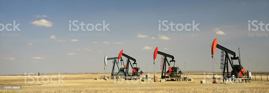 Panorama of a Row of Four Pumpjacks on the Great Plains stock photo