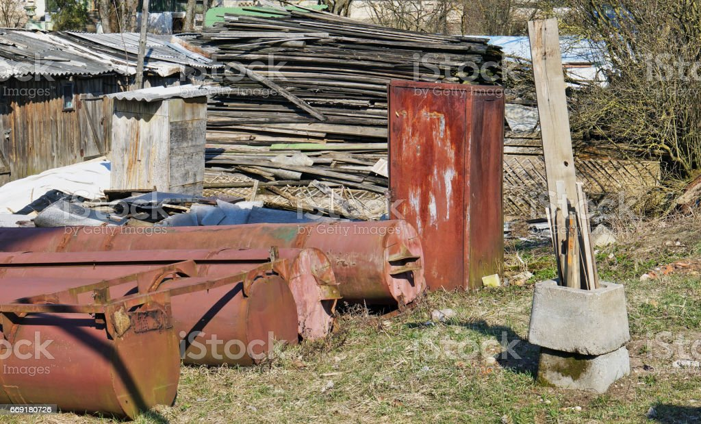 Panorama of a rural garbage dump - iron, boards, concrete blocks, plastic foil. Sunny sping day rustic  landscape stock photo