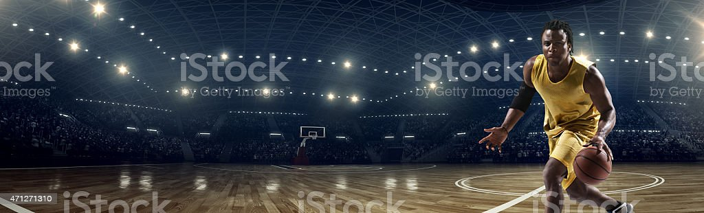 Panorama of basketball stadium under lights with player stock photo