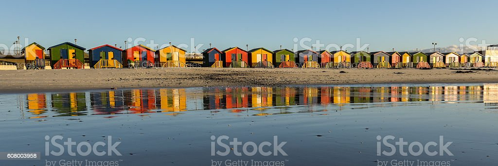 panorama of cabanas seen from the water reflecting in sand. stock photo