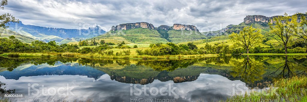 panorama of flat-top mountains and green hills reflected in water stock photo