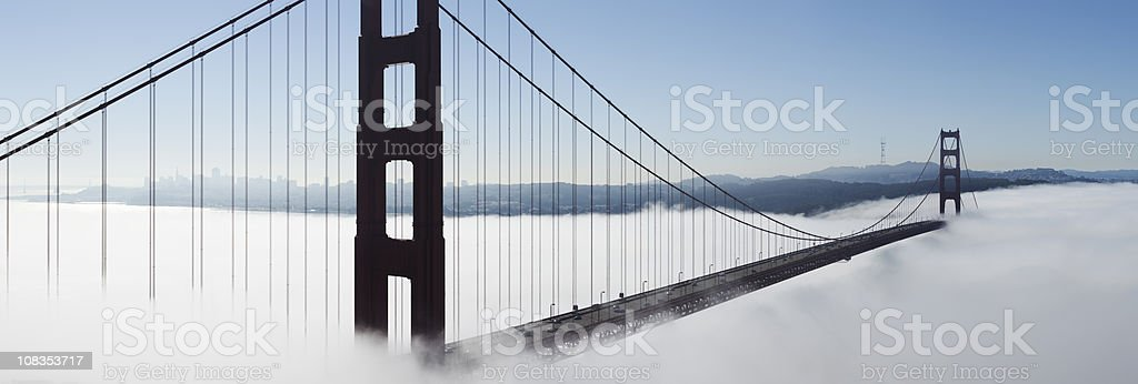 Panorama of Golden Gate Bridge floating in fog stock photo