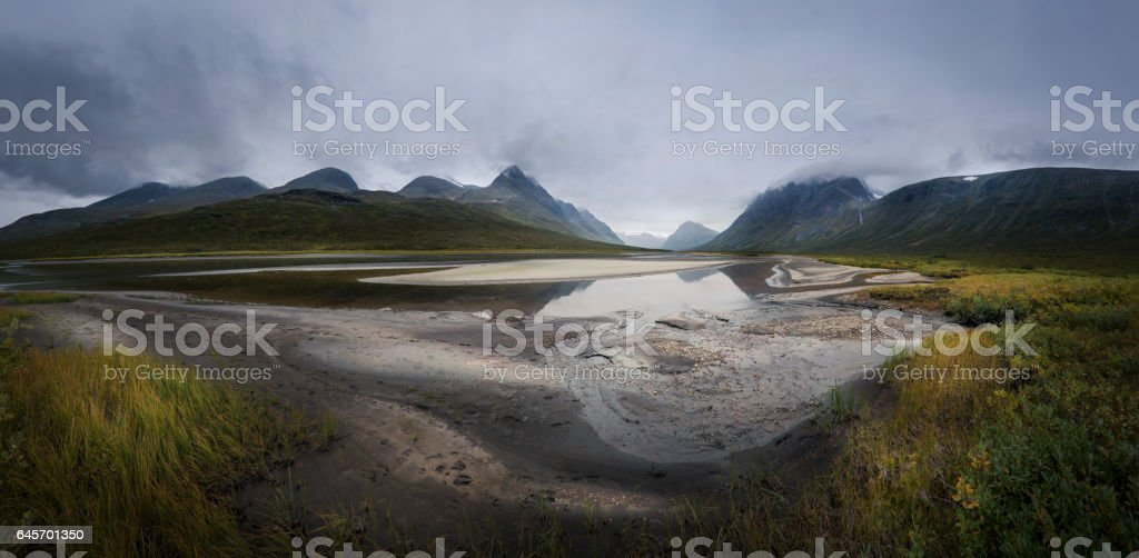 Panorama of Rapadalen river valley in dark and moody clouds landscape, Sweden stock photo