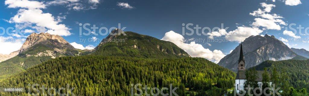 panorama of Scuol catholic church and Lischana stock photo