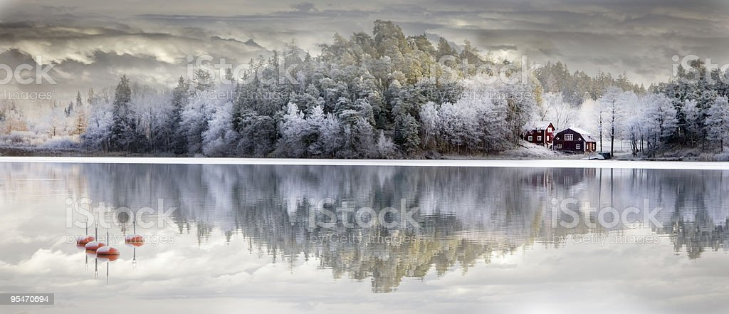 Panorama of snow covered trees and house with reflection stock photo