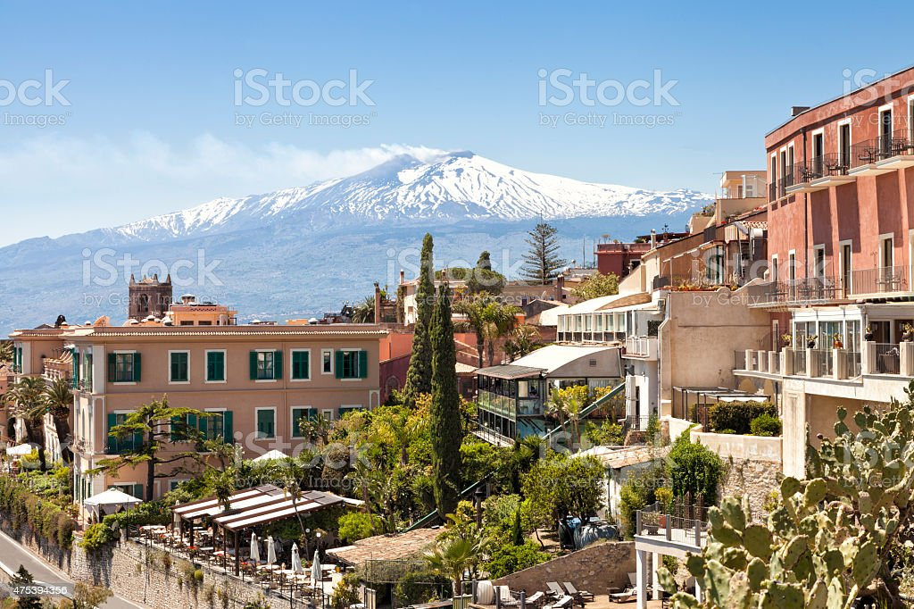 Panorama of Taormina with white peak of smoking volcano Etna stock photo