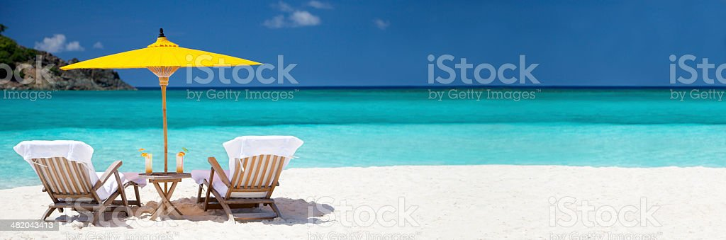 panorama of teak steamers under umbrella at a tropical beach stock photo