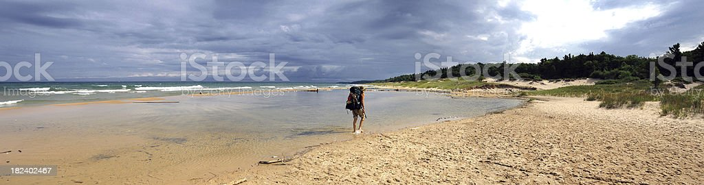 Panorama of Woman Backpacking Along Beach royalty-free stock photo