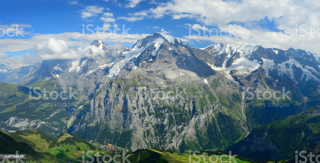 Panorama view of the famous peaks: Eiger, Monch and Jungfrau of Swiss Alps on Bernese Oberland, form top of Schilthorn, Canton of Bern, Switzerland. stock photo