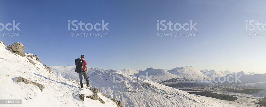 Panoramic of a male hiker standing in snowy hilly landscape royalty-free stock photo